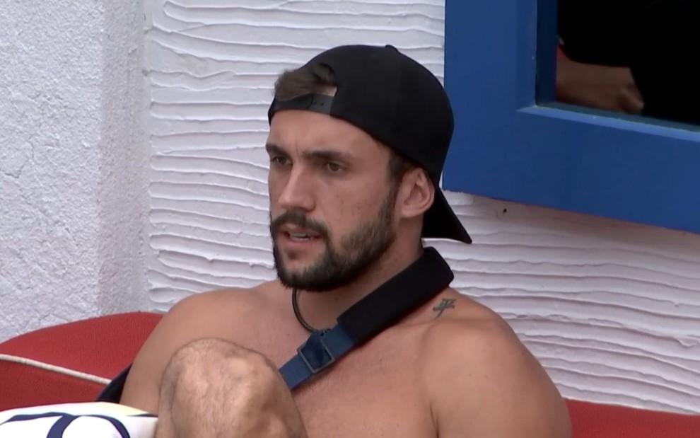 Arthur Picoli, participante do BBB21, usando boné e tipoia, sem camisa, durante conversa com olhar sério