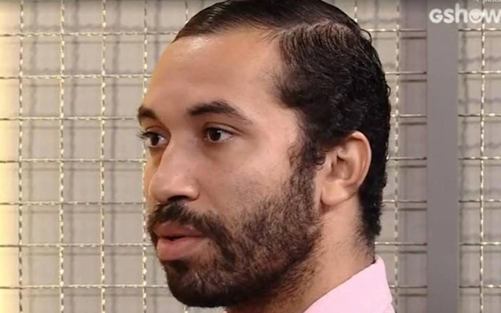 Gilberto Nogueira olha para o lado, está com o semblante fechado e usa camiseta rosa