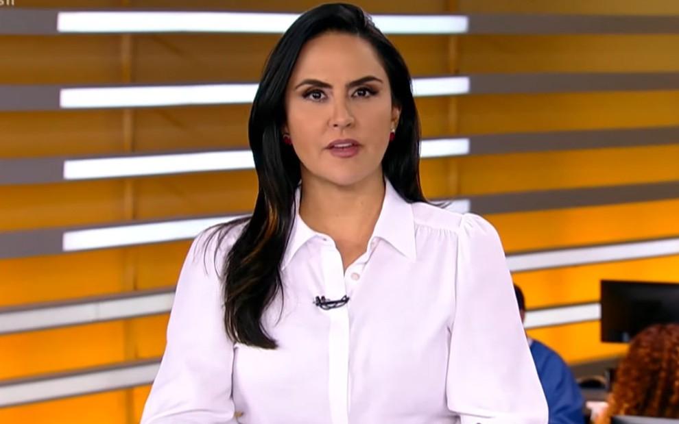 Carla Cecato com uma camisa branca na bancada de um telejornal
