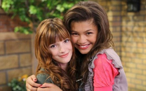 As atrizes Bella Thorne (à esq.) e Zendaya sorriem abraçadas como as personagens CeCe e Rock, respectivamente, na série No Ritmo