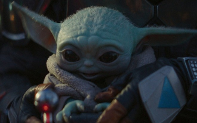 Baby Yoda esbanja fofura no colo do personagem principal de The Mandalorian