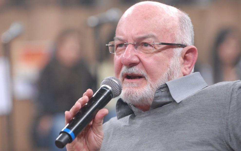 Silvio de Abreu segura microfone no cenário do Altas Horas