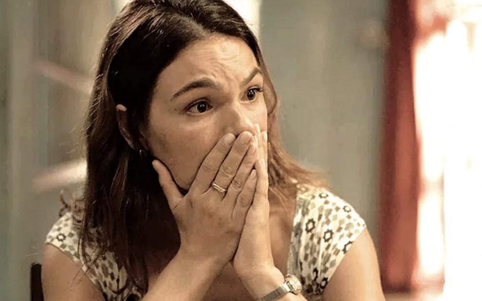 Em um close em seu rosto, a atriz Isis Valverde leva as mãos a boca, em sinal de surpresa, caracterizada como a Betina em cena de Amor de Mãe
