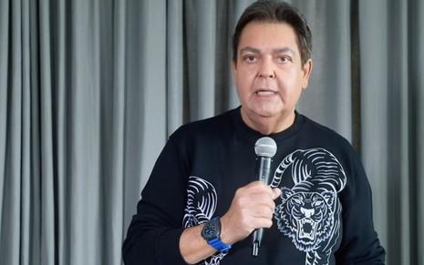 O apresentador Fausto Silva introduz o Domingão do Faustão do dia 5 diretamente de sua casa, com cortina ao fundo
