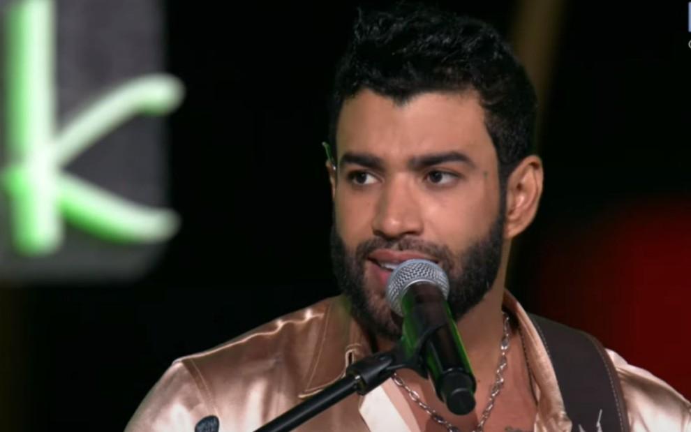Gusttavo Lima em frente a microfone durante live transmitida pelo YouTube