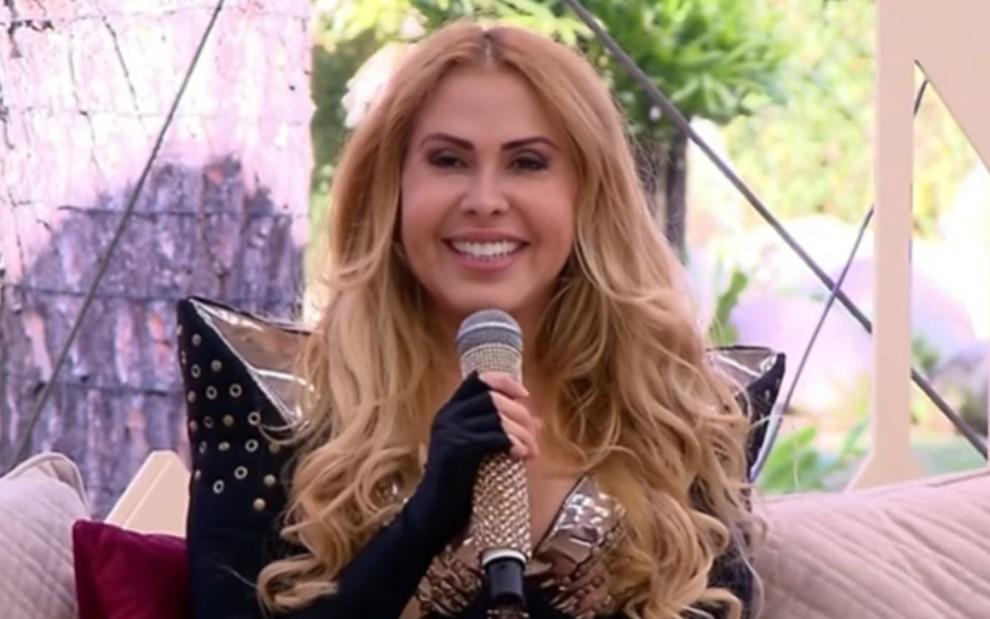 Joelma usa roupas pretas no estúdio do Vem Pra Cá, do SBT, enquanto sorri e segura o microfone