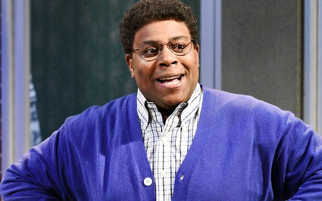 Kenan Thompson de blusa roxa e óculos de grau no humorístico Saturday Night Live