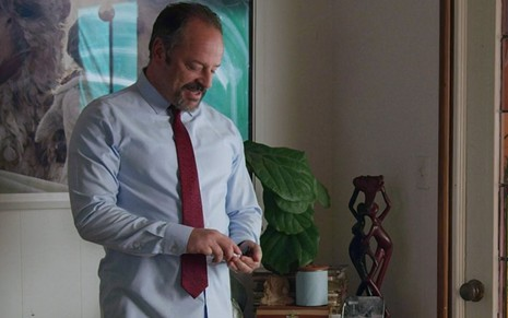 Usando camisa de manga longa e gravata, Gil Bellows usa álcool gel na mão esquerda em em cena da minissérie Love in the Time of Corona