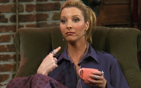 Lisa Kudrow como Phoebe Buffay no sofá do Central Perk da série Friends
