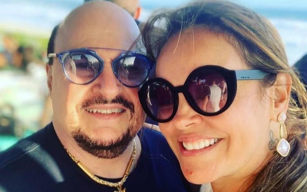Paulinho e Elaine sorridentes, ambos de óculos escuros