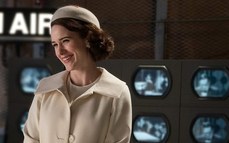 Rachel Brosnahan em frente a televisores antigos em cena de The Marvelous Mrs. Maisel, do Prime Video