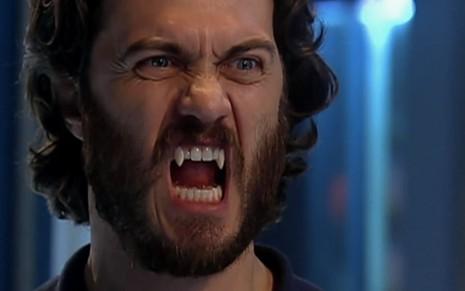 O ator Gabriel Braga Nunes com cabelos e barba grandes, caninos afiados, como um vampiro em cena de Os Mutantes