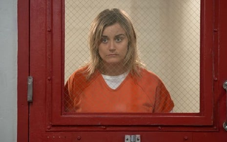 Taylor Shilling atrás das grades como Piper Chapman em cena da série Orange Is the New Black