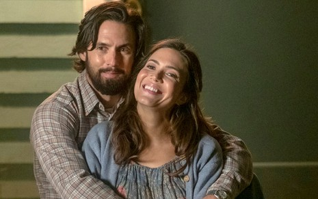 Barbudo e cabeludo, Milo Ventimiglia abraça uma sorridente Mandy Moore na quarta temporada de This Is Us