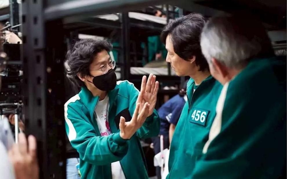 O diretor da série da Netflix Round 6, Hwang Dong-hyuk , está no set conversando com os protagonistas da série. Todos estão de verde, vestindo o uniforme que os personegens vestem em Round 6.