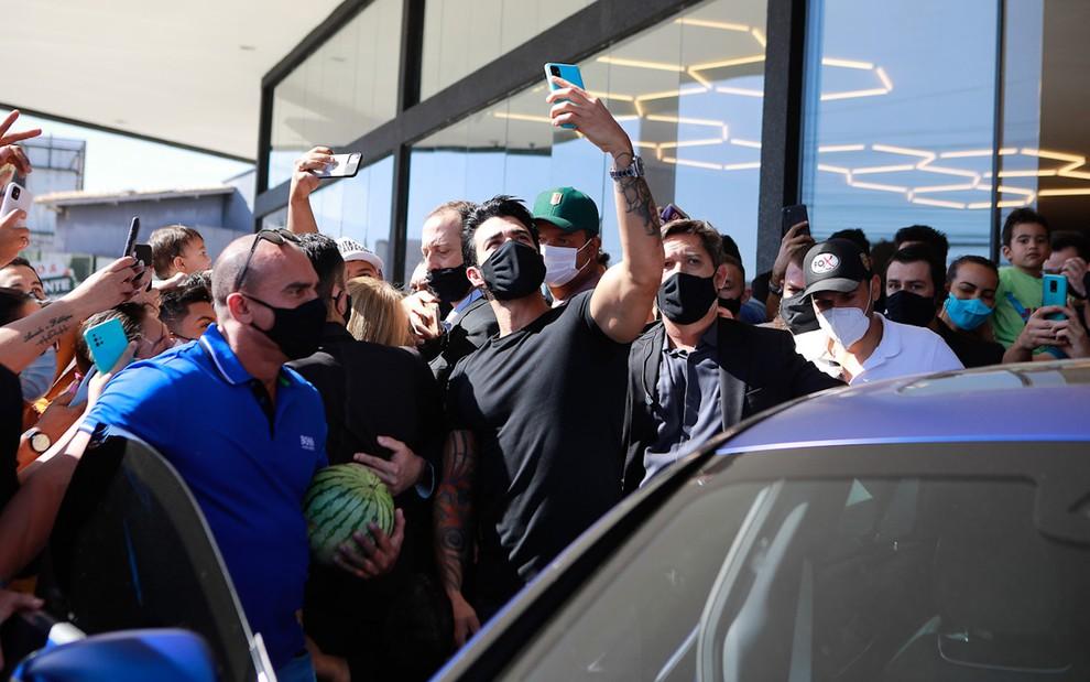 Com máscara e blusa pretas, o sertanejo Gusttavo Lima tira fotos com fãs e é escoltado por seguranças