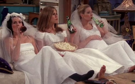 As atrizes Courteney Cox, Jennifer Aniston e Lisa Kudrow sentadas no sofá vestidas de noiva e bebendo cerveja em cena de Friends