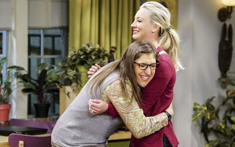 As atrizes Mayim Bialik e Kaley Cuoco se abraçam em episódio da 11ª temporada de The Big Bang Theory