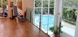 Academia da mansão de Xuxa, com vista para a piscina externa (Foto: Judice & Araujo/Divulgação)